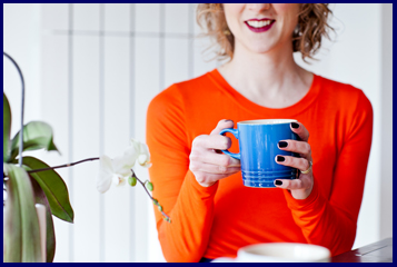 Susannah The Shoe Consultant holding a cup of tea with orchid plant in shot