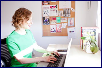 Susannah The Shoe Consultant typing at a laptop with shoe pictures in the background