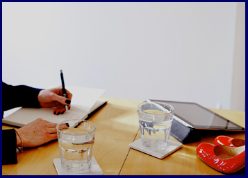 Woman writing in a notebook with red shoes and ipad and glasses of water on the table